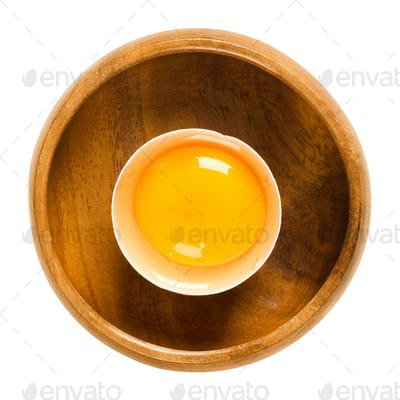 Open raw chicken egg in wooden bowl over white