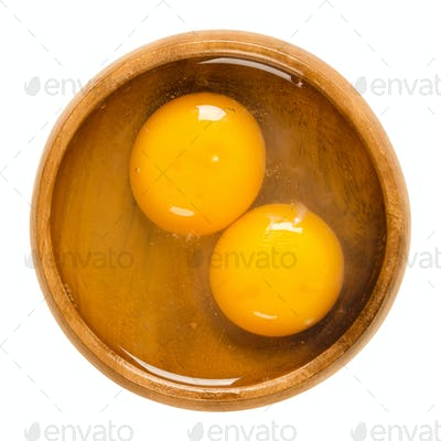 Two raw chicken eggs cracked into a wooden bowl