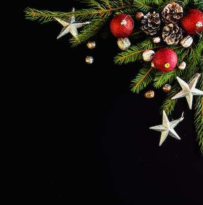 Christmas background with balls, silver nuts and stars, fir tree branches on black