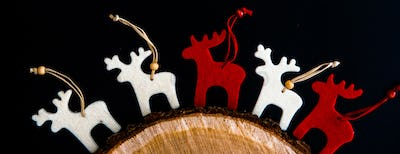 Red and white felt rein deers isolated on black. Christmas background with handmade ornaments