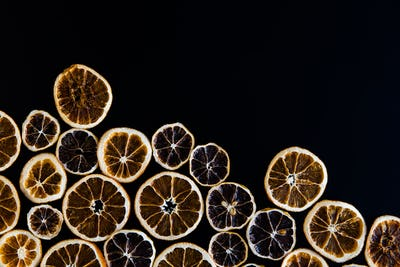 Abstract background of dried orange slices on black