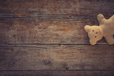 Teddy bear on toned wooden background. Space for text