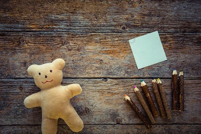 Teddy bear, sticky note and colored pencils on wooden background