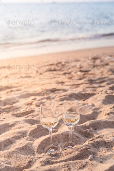Two glasses of white wine on the beach at the summer sunny day.