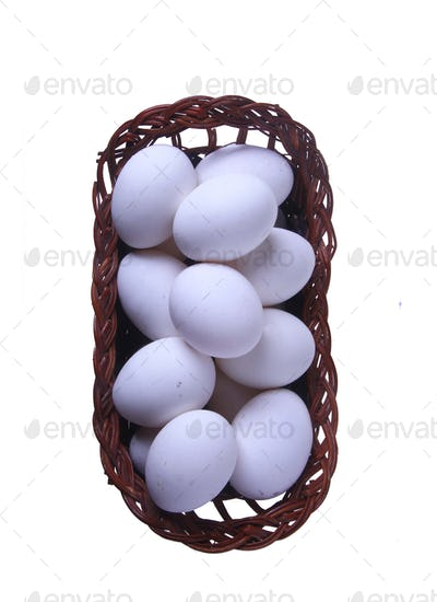 Eggs in a straw basket top view isolated