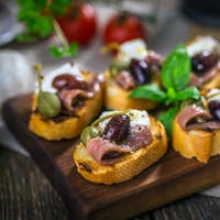 Tasty bruschetta with anchovy,  feta, caper, olive oil ...