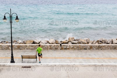 Man exercising and running on city street at seaside