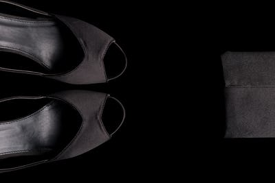 Fashion Lady Accessories Set. Minimal. Black Shoes and bag on black background. Flat lay.