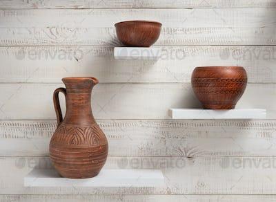 clay jug and plate at shelves