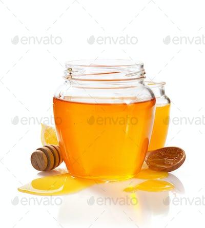 glass jar full of honey and dipper
