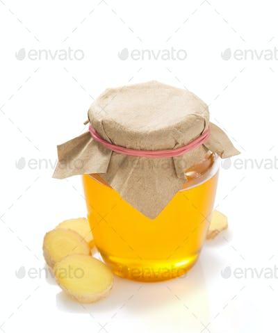 jar of honey and ginger on white background