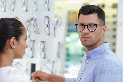 male optician consulting young customer near sunglasses display