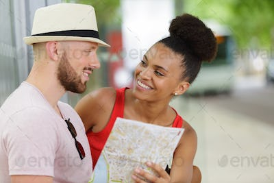 good looking couple lost in city reading map