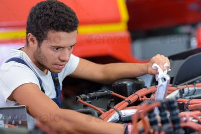 young man trying to repair a car engine