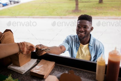 african american man buying wok at food truck