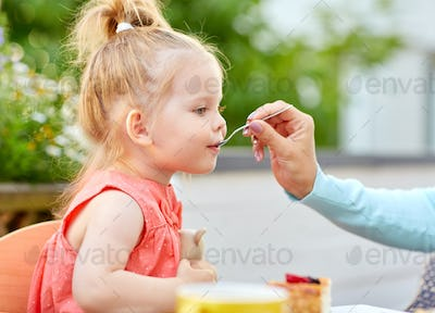 mother hand with spoon feeding daughter at cafe