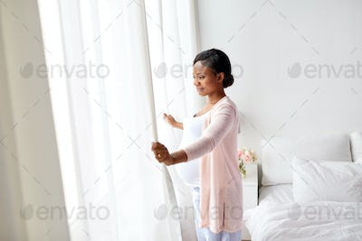 pregnant woman looking through window at home