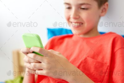 close up of happy boy with smartphone at home