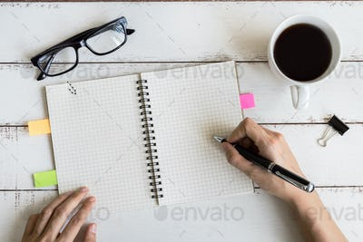 Cup of coffee with notebook and copy space on white wooden desk