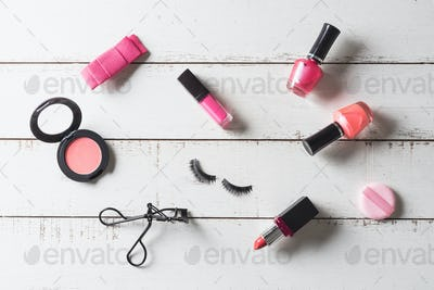 Various make-up products and cosmetics on wooden table