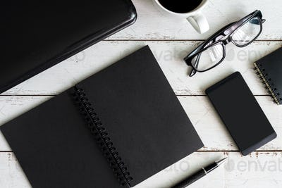 Notebook with laptop and cup of coffee on office desk