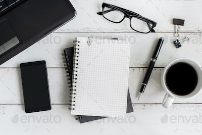 Notebook with laptop and cup of coffee on wooden desk