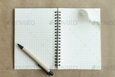 Blank notebook with pen on brown background