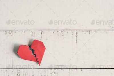Red broken heart on white wooden background