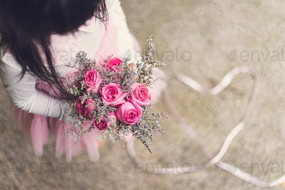 Little girl holding bouquet of rose