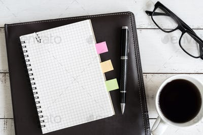 notebook with cup of coffee on office desk