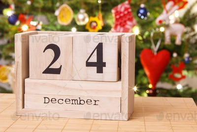 Date 24 December on calendar, festive tree with decoration in background, Christmas eve time concept