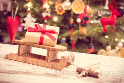 Gift with ribbon on wooden sled for Christmas and tree with decoration