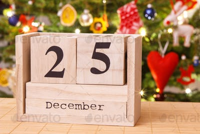 Date 25 December on calendar, festive tree with decoration in background, Christmas time