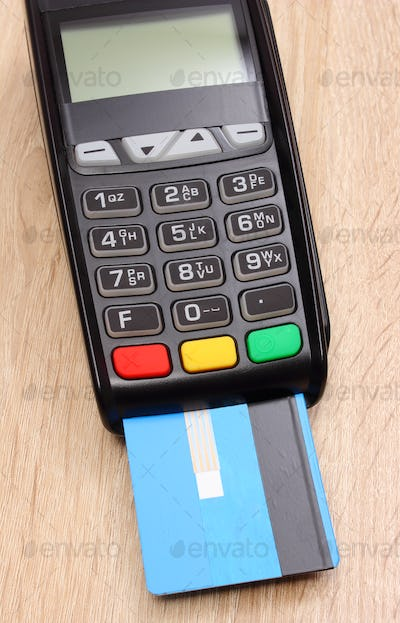Payment terminal with credit card on desk, paying for shopping concept