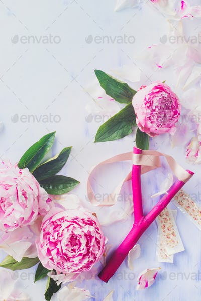Bright pink slingshot with pink peony flowers on a light wooden background
