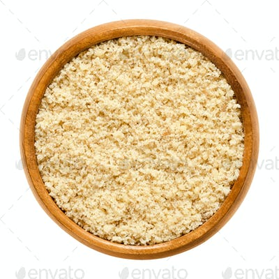 Ground walnuts in wooden bowl over white