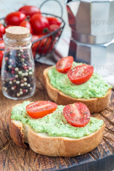 Open sandwich with mashed avocado and cherry tomatoes, vertical