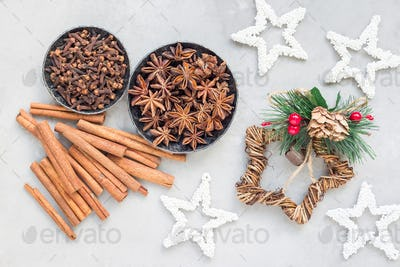 Different kinds of winter spices in bowls, christmas decoration on background, horizontal