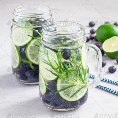 Healthy cold infused water with fresh blueberry, lime and rosemary, square