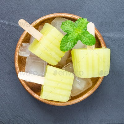 Homemade melon popsicles on grey slate, top view, square
