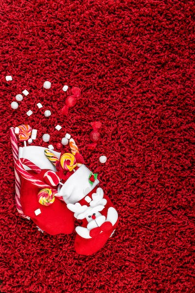 Christmas socks full of candy and sweets on red fleecy background. Flat lay. Copy space.