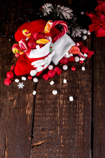 Christmas socks full of candy and sweets on wooden background.