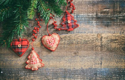 Christmas ornaments and green garland on a wooden board