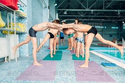 Boys doing sportive exercises in pairs near pool.