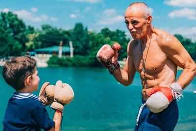 Little boy practicing boxing with grandfather
