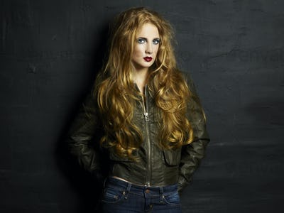Portrait of a young redheaded woman in a leather jacket