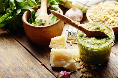 Pesto sauce ingredients and utensils on wood table
