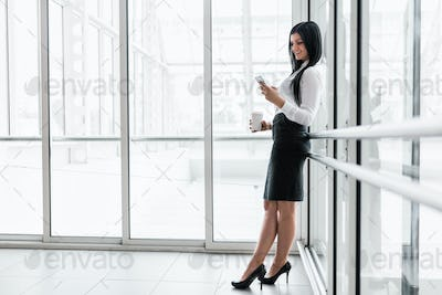 Successful business woman with coffee and smartphone in an office setting