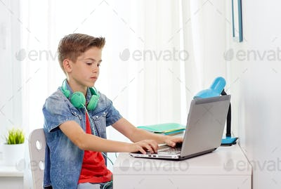 boy with headphones typing on laptop at home