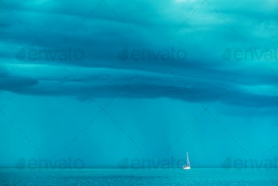 Sailing boat at stormy sea horizon